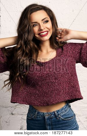Young beautiful gorgeous female model in blue jeans and purple pullover posing against white brick wall. Stunning glamorous happy joyfull smiling girl with long curly hair