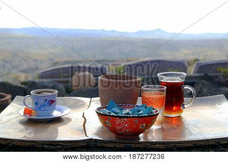Travel To Cappadocia, Turkey. The Cup Of Turkish Tea And Coffee On The Wooden Table In The Mountains