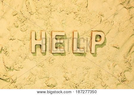 Help message in block letters on the sand.
