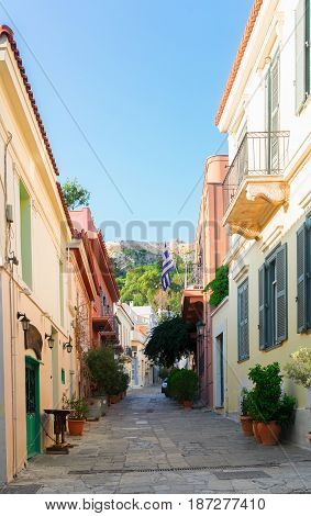 small cosy street of Placa district with Acropolis hill in Athens, Greece