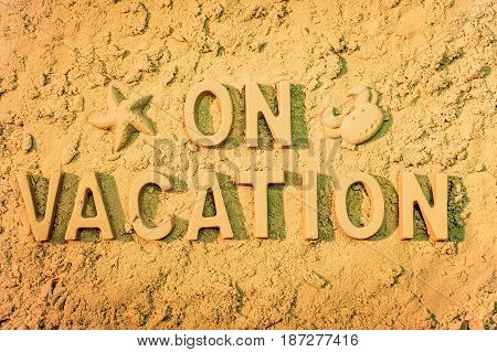 On vacation message in block letters on the sand.