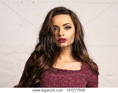 Young beautiful gorgeous female model inpurple pullover posing against white brick wall. Stunning glamorous girl with long curly hair