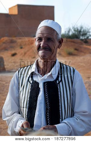 GHARJAN LIBYA SEPT 27 2009: Libya; An elderly Libyan vendor in traditional clothes near the entrance to the traditional Berber house
