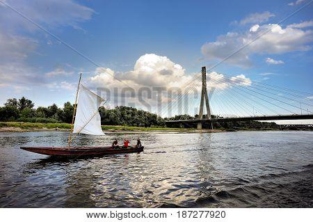 POLAND WARSAW - Aug 11 2013 Modern Swietokrzyski bridge in Warsaw over Vistula river with yacht in the foreground Poland