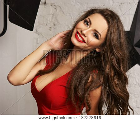 Young beautiful pretty sexy woman with long curly hair and red lips in red blouse. Happy girl portrait against white brick wall