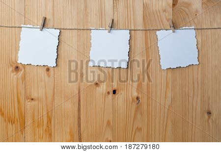 Three jagged note with clothes pegs on a cord on wood