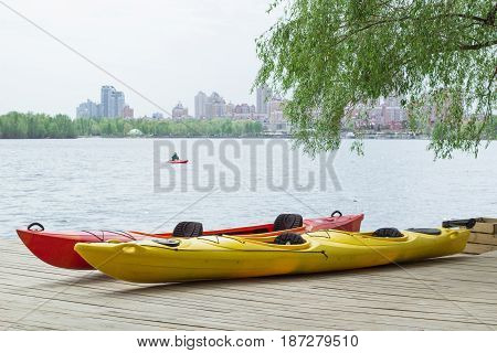 Two Kayaks On Wooden Deck At Station Near Lake