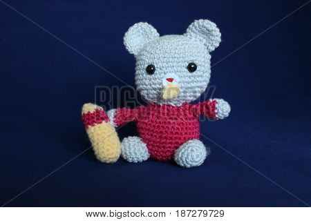 Woolen toy made in crochet and hand on blue background