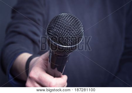 Journalist making speech with microphone and hand gesturing concept for interview. Selective focus on microphone.
