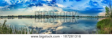 Lake-shore image, reed, cloudy sky, infrared sunshine, pre-storm silence