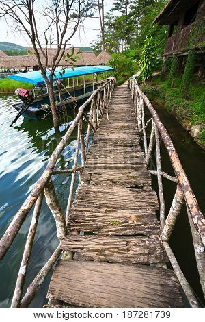 Wooden bridge on lake and standing in the water the boat of the national huts of Thailand.