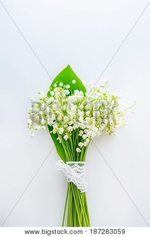 Beautiful Bouquet Of Lilies Of The Valley, May-lily Flowers With Lace Ribbon On The White Background