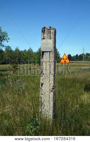 Soviet vintage geodesic sign.Radioactivity sign behind.May 19, 2017.Chernobyl area.Kiev region.Ukraine