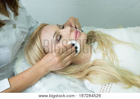 Beautiful young girl on facial cleansing procedure in cosmetology