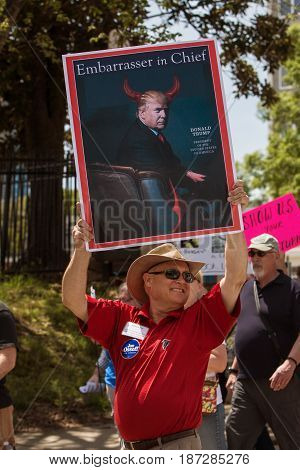 ATLANTA, GA - APRIL 2017:  A man holds up a sign that shows Donald Trump and says