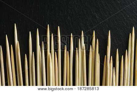 Toothpick on a black background. Not an even number. View from above.