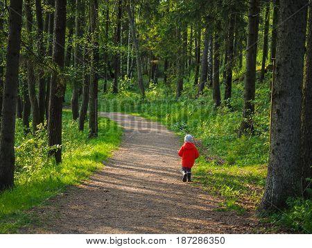 Unrecognizable little boy in a big orange jacket running along on a forest