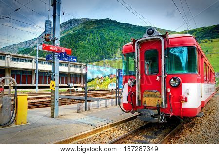 ANDERMATT, SWITZERLAND, AUG,19, 2010: Railway station and Bernina Express mountain train red passenger coaches Alpine train mountains. Swiss train to Matterhorn Alps Swiss holidays vacations tours