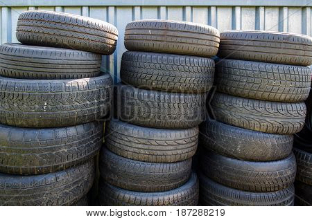 three stacks of used old tires in front of a container