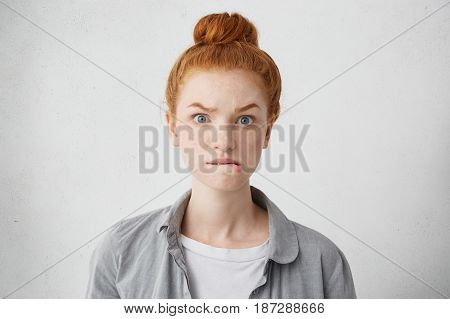 Headshot Of Anxious Redhead Freckled Caucasian Girl Raising Eyebrows And Biting Lower Lips Having Sc