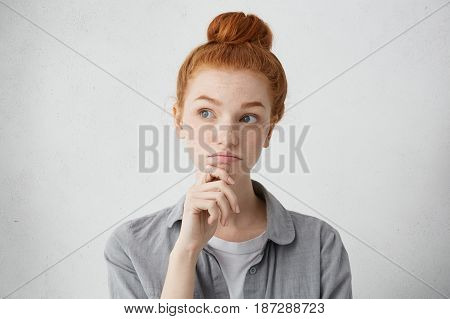 Portrait Of Charming Young Red Haired Lady Looking Away With Doubtful Expression, Holding Hand On He