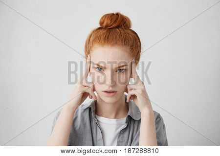 Close Up Shot Of Stressed Unhappy Young Caucasian Woman Wearing Her Ginger Hair In Bun, Keeping Fing