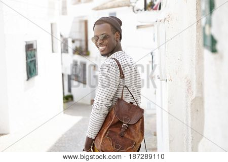 Rear View Of Attractive African American Tourist Wearing Shades, Hat And Leather Backpack On Shoulde