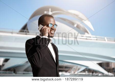 Successful Dark-skinned Businessman Wearing Elegant Black Suit And Round Sunglasses Having Pleased S
