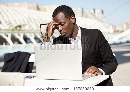 Young Dark-skinned Office Worker Dressed In Formal Clothes Sitting With Closed Eyes Outdoors In Fron