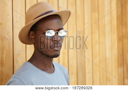 Outdoor Portrait Of Attractive Trendy-looking Young Afro American Man With Faint Smile Wearing Styli