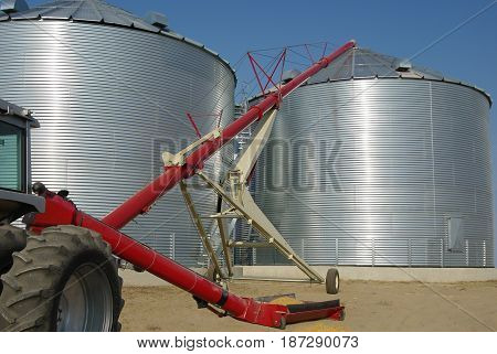 Storing Grain:  A tractor-driven auger transfers grain from a tray at ground level to the top of a storage bin on a farm in South Dakota.