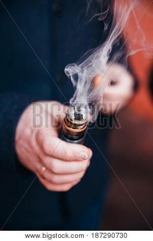 close-up of an electronic cigarette a vape is going to steam with a fragrant liquid on the fleece. The spiral is hot. The concept of replacement of cigarettes with tobacco, harmless smoking.