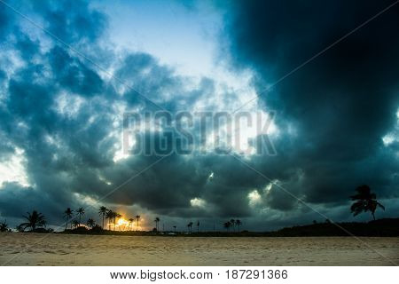 Sunset on the beach with storm clouds while the sun is hiding among the dunes