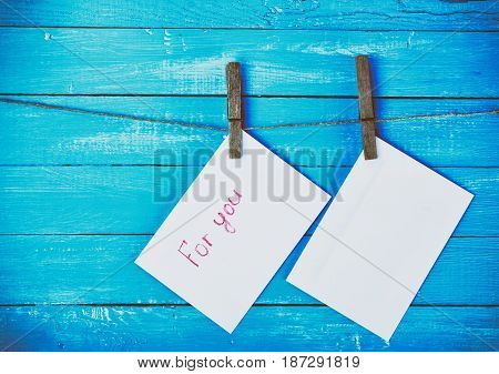 Two envelopes whistling on a rope and fixed with wooden clothespins vintage toning