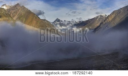 Fog Into The High Mountains: Gray Clouds Lie Below The High Colored Peaks With Snow On The Peaks, Su