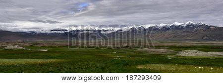 High Mountain Valley Of Tibet In Summer: Chains Of High Peaks With Snow On Peaks And Huge Green Past