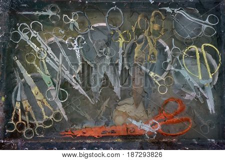 Art still life with a large number of different scissors: old scissors medical scissors manicure scissors orange gray silver and gold color distortion of silhouettes due to water unusual design.