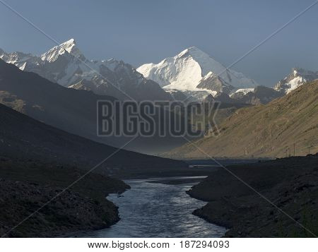 Dawn in the mountain valley: the sun lit up the high snow-white peaks the foreground is still in the shade but the blue water of the river glares Tibet the Himalayas India.