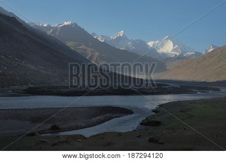 Morning sun moves along the mountain valley: in the foreground the riverbed with branches and further high illuminated peaks with a snow glacier on tops the Himalayas India.