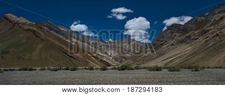 Panoramic photo high mountains of the valley of the Zanskar river beautiful mountain chains pebble bottom of the river to the foreground the Himalayas Northern India.