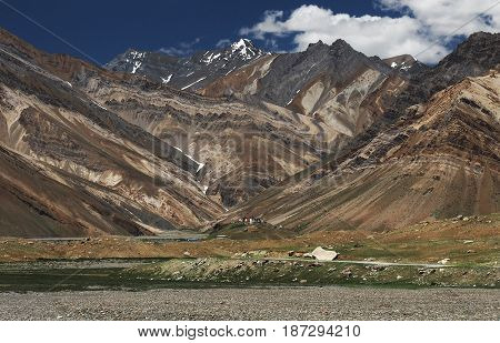 Majestic beautiful high mountains of the valley: folds of mountains of a different brown shade create a beautiful figure on a small hill stands a Buddhist monastery Zanskar Northern India.