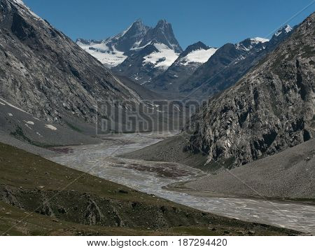 Winding gray moraine valley of the high mountain glacier: from the highest peaks covered with crusts of ice descends a delicate stream of the river summer in Zanskar India.