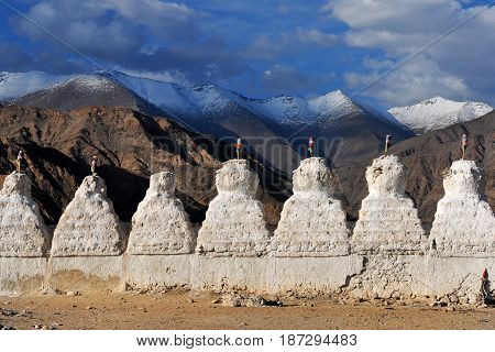 A row of white ancient Buddhist stupa on the background of the high brown mountains of Tibet a clear sunny summer evening Ladakh Northern India.