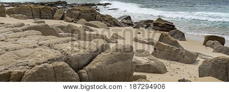 Australian panoramic rocky seafront beach view with rocks boulders sand beach surf waves and ocean