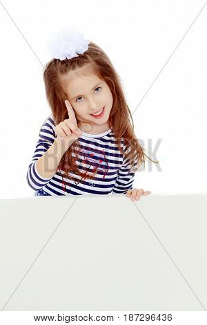 The little blonde girl with long hair and with a white bow on her head , in a blue striped summer dress.She peeks out from behind white banner, and a threatening finger.Isolated on white background.