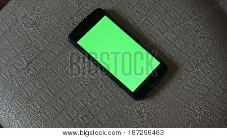Smartphone with a green screen rests on a chair.