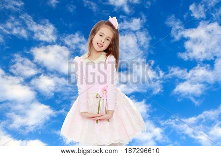Dressy little girl long blonde hair, beautiful pink dress and a rose in her hair.She folded their hands in front of him.On the background of summer blue sky and fluffy clouds.