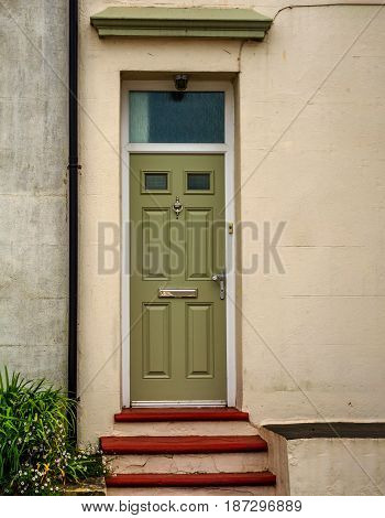Entrance To A Residential Building, Green Door With Windows, Plant In Pot And Beautiful Stairs