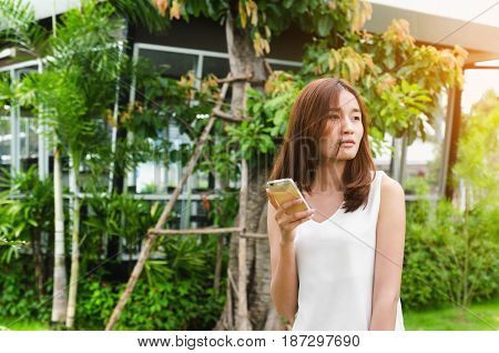 Beautiful women in the park using mobile shopping online