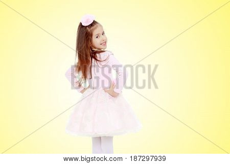 Dressy little girl long blonde hair, beautiful pink dress and a rose in her hair.She turned her back to the camera and looks over his shoulder.On a yellow gradient background.